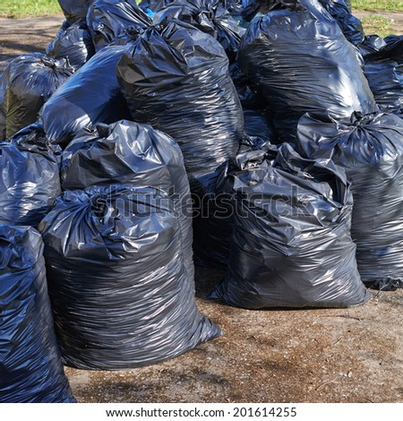 Pile of black plastic garbage bags on the ground - stock photo