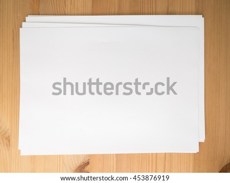 Pile of blank paper on wooden office desk. - stock photo