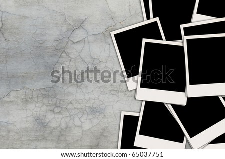 Pile of Blank Photos on Grey Shabby Concrete Wall with Copy Space