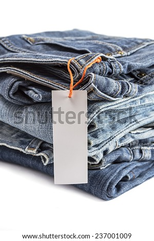Pile of blue jeans with tag label isolated on white background. Selective focus on tag label. - stock photo