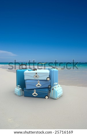 Pile of blue luggage on a tropical beach - stock photo