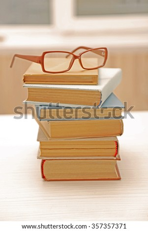 Pile of books and eyeglasses on it, close up - stock photo