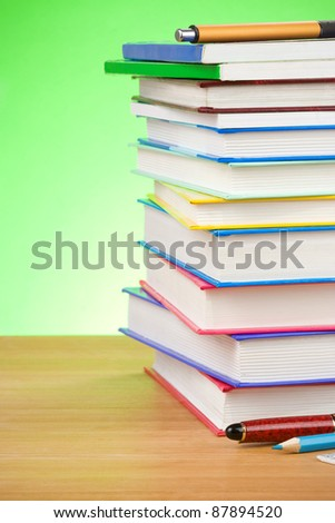 pile of books and pen on green background