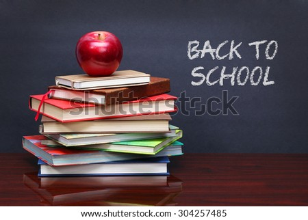 Pile of books and red apple on the desk. The words 'Back to School' written in chalk on the blackboard