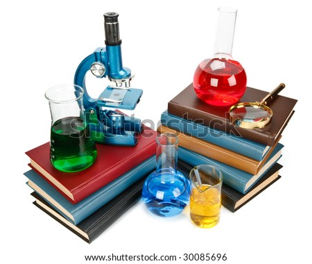 Pile of books, flasks, microscope and magnifier on a white background - stock photo