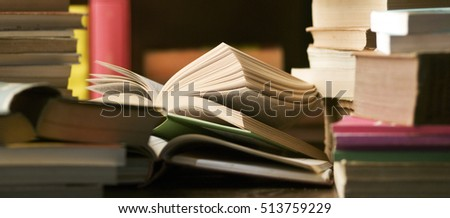 pile of books in a library and on a desk