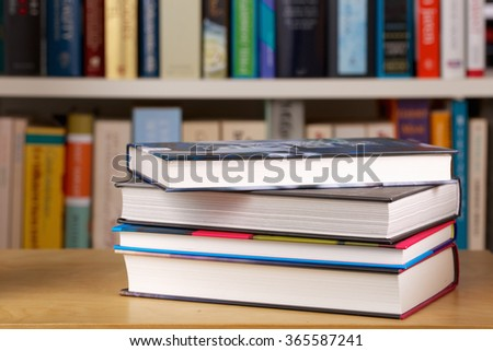 Pile of books in a library. Bookshelf in the background. - stock photo
