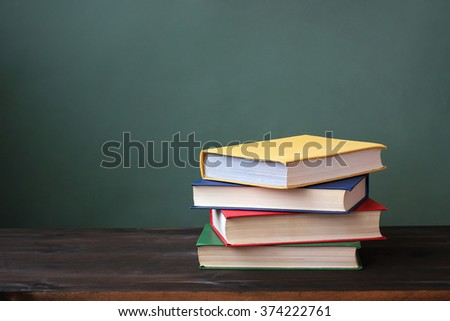 Pile of books in color covers on a dark wooden table. - stock photo