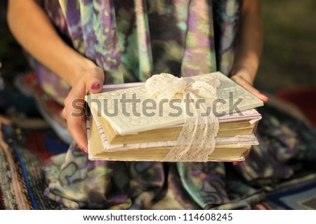 Pile of books in hands. Book with a white envelope tied with lace ribbon - stock photo