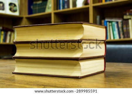 pile of books in kibrary, close-up, old, on wooden table - stock photo