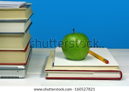 pile of books, laptop, green apple and pencil - stock photo
