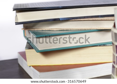 Pile of books on a wooden desk and white background