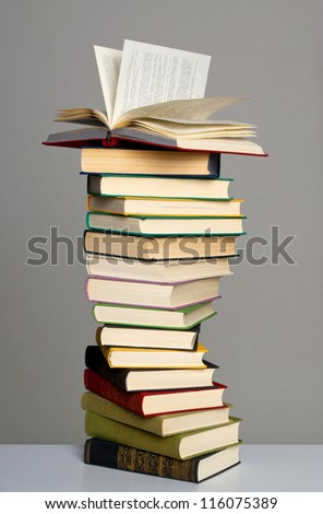 Pile of books on grey background - stock photo