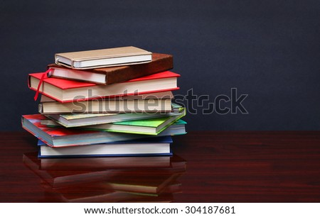 Pile of books on the desk over the blackboard - stock photo