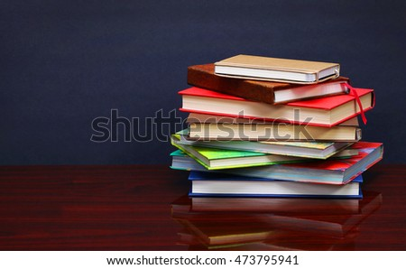 Pile of books on the desk over the blackboard
