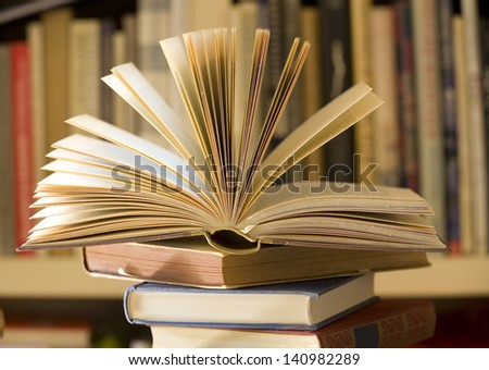 pile of books, one open, selective focus