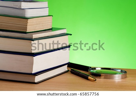 pile of books, pen and magnifier on wood table - stock photo