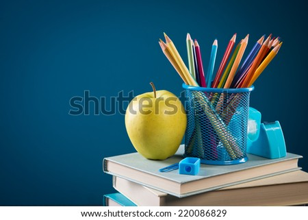 Pile of books with color pencils and apple, back to school concept.