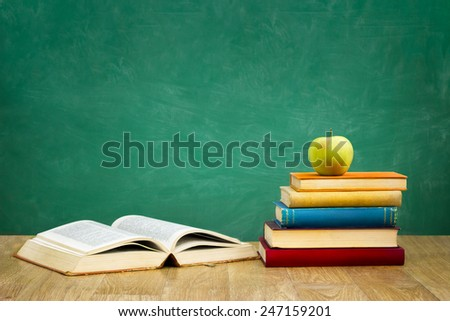 pile of books with one book open on empty green  school board background - stock photo