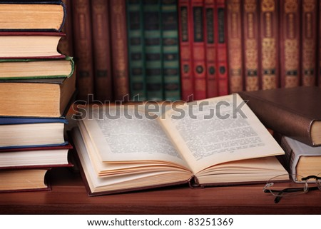 Pile of books with reading glasses on desk - stock photo