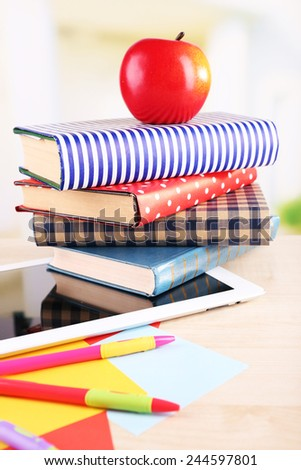 Pile of books with tablet on wooden table and light background - stock photo