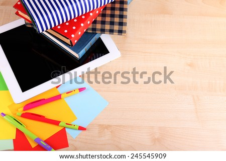 Pile of books with tablet on wooden table background - stock photo