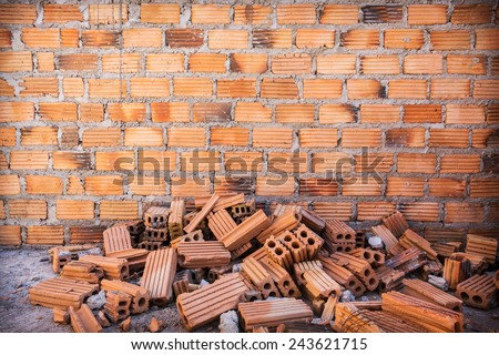 pile of bricks in construction site with brick wall background - stock photo