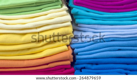 Pile of bright folded clothes.t-shirts - stock photo