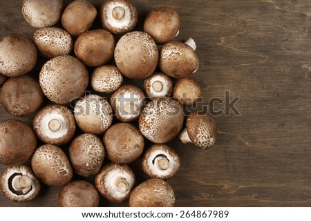 Pile of brown cap mushrooms on rustic wooden background. Top view point.  - stock photo