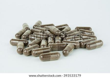 Pile of brown herbal capsules - stock photo