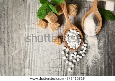Pile of brown sugar cubes and stevia  on grey wooden background - stock photo