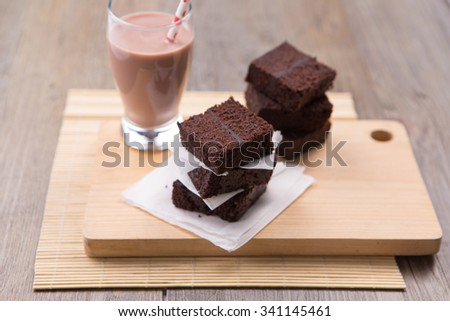 Pile of brownies with chocolate milk on the cutting board and wood table - stock photo