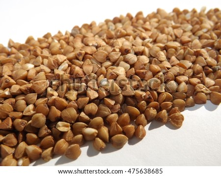 pile of buckwheat groats on the white background