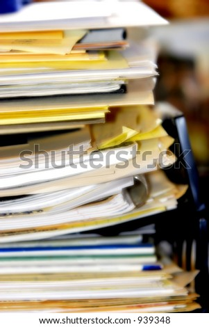 Pile of business/healthcare paperwork and/or forms stacked in an overflowing inbox. - stock photo
