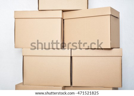 pile of cardboard boxes near the white wall