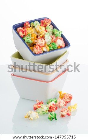 Pile of ceramic bowls of popcorn on white reflective background.
