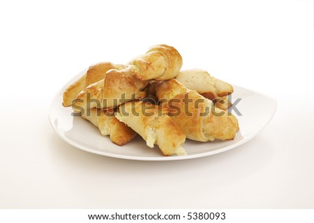 Pile of cheese filled pastry rolls over a white background