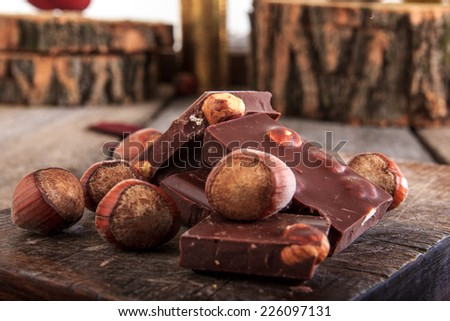 Pile of chocolate pieces with hazelnuts on wooden background close up - stock photo
