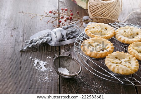 Pile of Christmas fruit mince pies and Christmas decorations over rustic wooden background - stock photo