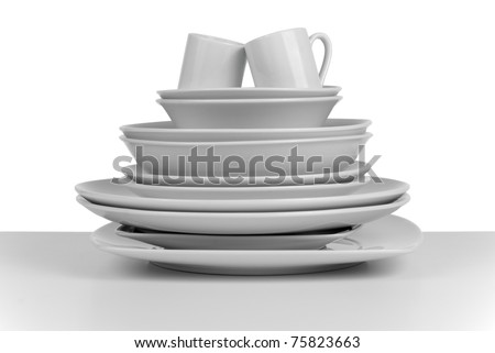 Pile of clean empty dishes and cups on white background.