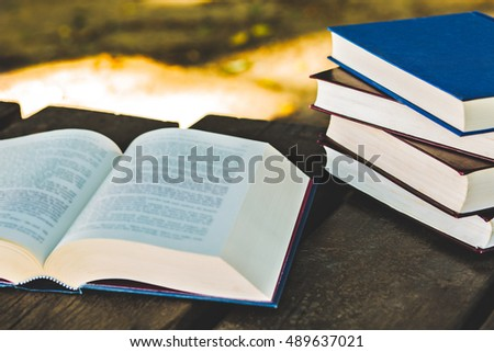 Pile of closed book with open book, outdoors.
