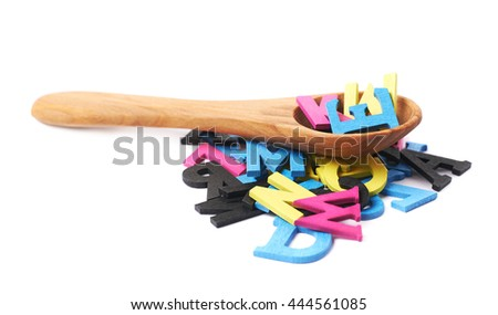 Pile of cmyk painted wooden letters with the wooden serving spoon over it, composition isolated over the white background - stock photo