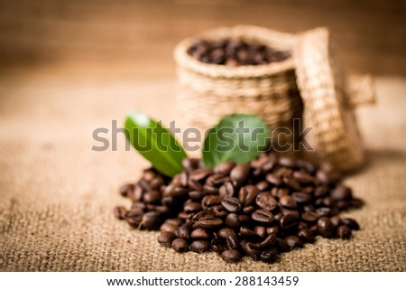pile of coffee beans and wooden spoon in jar with space for text - stock photo