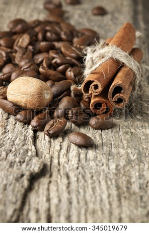 Pile of coffee beans, cinnamon sticks and nutmeg on old wood.  - stock photo