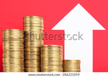 Pile of coins and growing arrow. More money. Increase income. Pile of 500 yen coins with growing arrow. Red background.  - stock photo