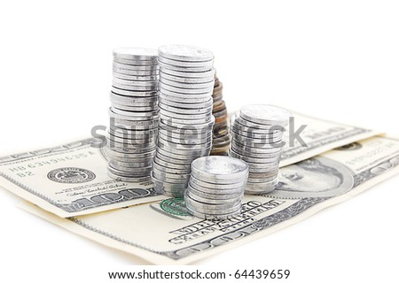 Pile of coins on dollar banknotes blue toned - stock photo