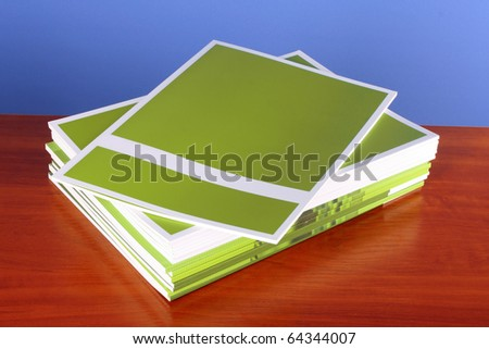 Pile of color magazines  on blue background - stock photo