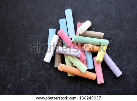 Pile of colored chalk on blackboard