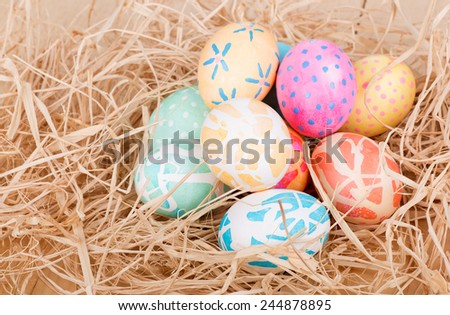 Pile of colored easter eggs on raffia - stock photo