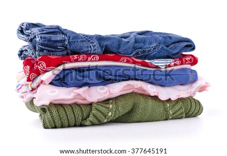 pile of colorful children's clothing on a white background - stock photo